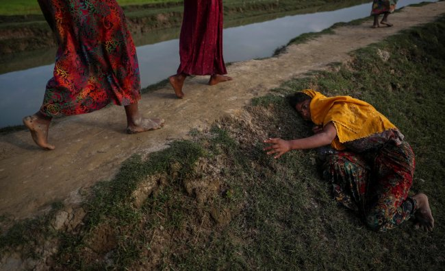 An exhausted Rohingya refugee fleeing violence in Myanmar cries for help from others crossing into Palang Khali, near Cox\'s Bazar, Bangladesh November 2, 2017. REUTERS/Hannah McKay