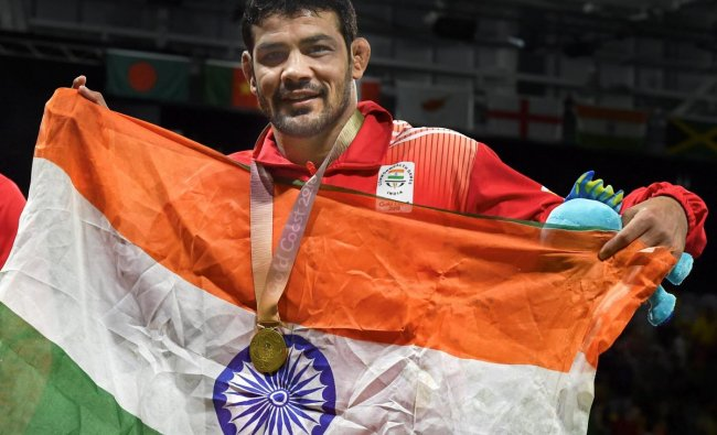 India\'s Sushil Kumar celebrates holding tricolour after winning a gold medal in the men\'s freestyle 74kg wrestling final bout against South Africans\' Johannes Botha at the Commonwealth Games 2018 in Gold Coast, on Thursday. (PTI Photo)