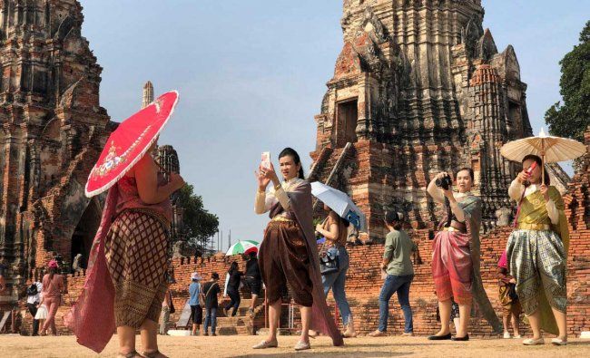 People dressed in traditional costumes pose for a picture, as interest for historical clothing rises within the country, in Ayutthaya, Thailand.