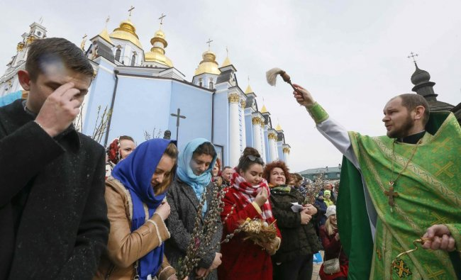 An Orthodox priest sprays holy water as believers mark the Palm Sunday in Kiev. Reuters Photo