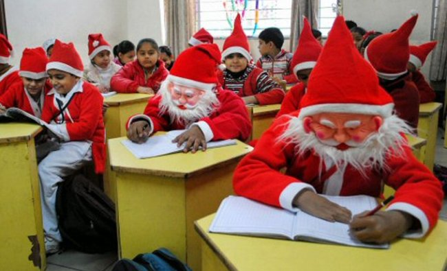 Students dressed as Santa Claus attend a class on the eve of Christmas festival in Gurgaon
