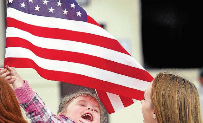 Heidi Cantrell waves an American flag while waiting for her father\'s return