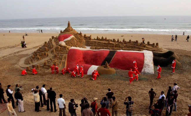 Students dressed as Santa creating sand sculpture of Santa Claus