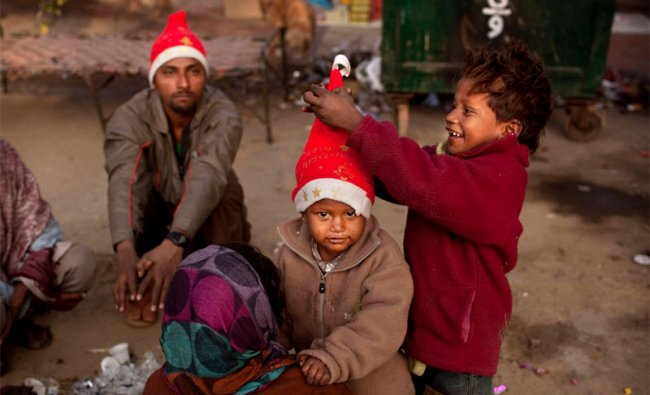 Children of homeless vendors in New Delhi play with festive hats on Christmas Day