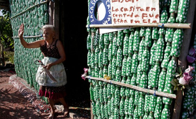 Maria Ponce, 78, stands in the doorway of her home constructed from recycled plastic bottles