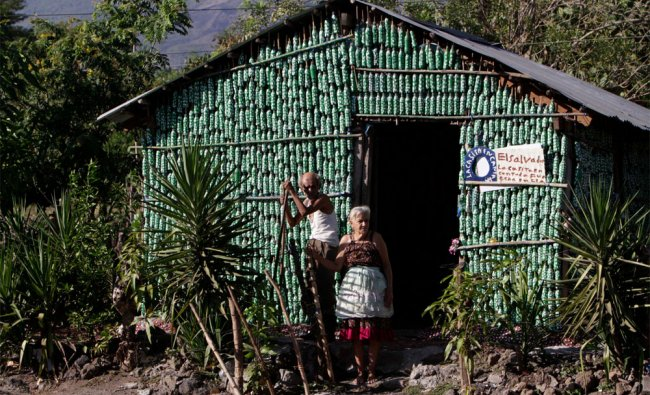 Prudencio Amaya and Maria Ponce stand in front of their home made from recycled plastic bottles