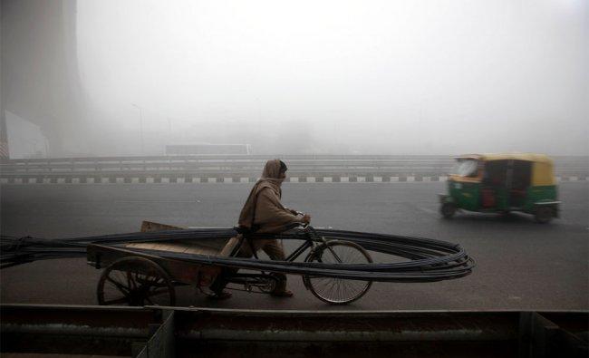 A rickshaw puller ferries iron rods for construction amidst dense morning fog, in New Delhi