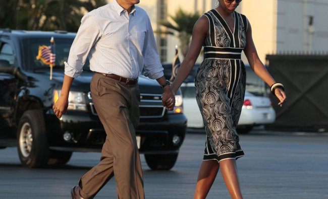 President Barack Obama and first lady Michelle Obama walks across the tarmac to board Air Force One