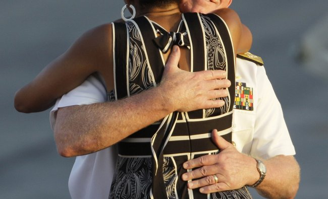 First Lady Michelle Obama is hugged by Admiral Robert Willard, Commander of the U.S. Pacific Command