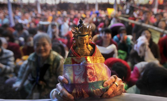A Chinese devotee holds an Idol as he and others listen to Tibetan spiritual leader the Dalai Lama