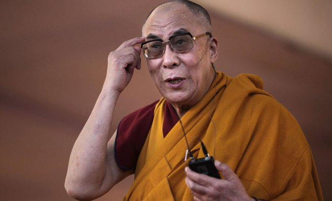 Tibetan spiritual leader the Dalai Lama gestures as he addresses devotees during a Buddhist festival