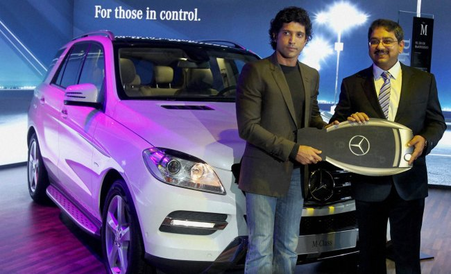 Actor Farhan Akhtar and an offcial of Mercedes pose with the company\'s M-Class car