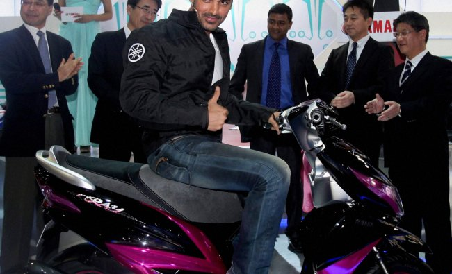 Actor John Abraham poses with a Yamaha Scooter Prototype model