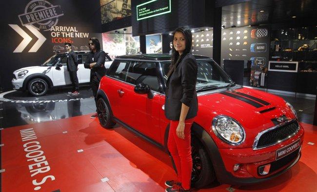 Models pose near Mini Cooper cars