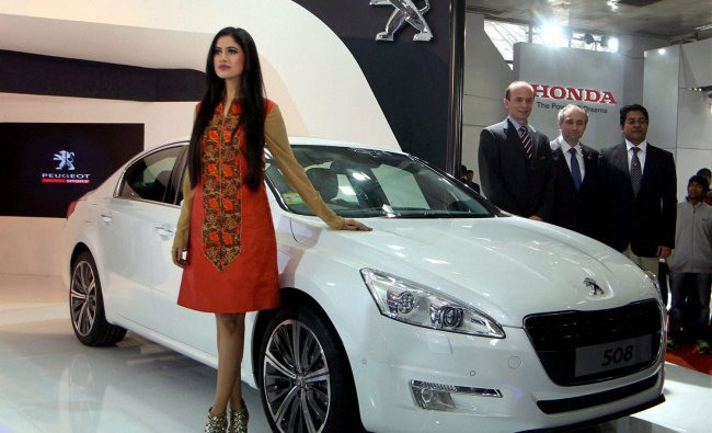 A model poses with Peugeot 508 car at the 11th Auto Expo 2012