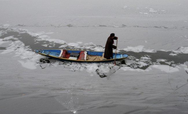 A Kashmiri boy rows a traditional boat on the Dal Lake