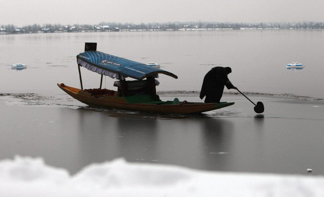 A Shikarawala break the frozen part of the Dal lake to create a path for his boat