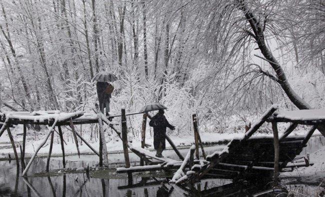 Kashmiris cross a foot-bridge as it snows on the outskirts of Srinagar