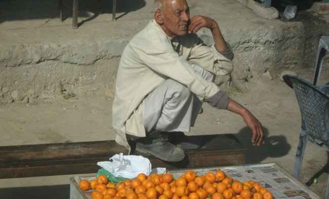 A Kashmiri from Rajouri sells fruits in front of Srinagar Airport, in biting cold