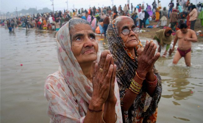 Elderly devotees pray at the confluence of the Ganges, Yamuna and Saraswati rivers