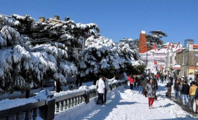 Tourists enjoy at the snow-clad Mall Road ...