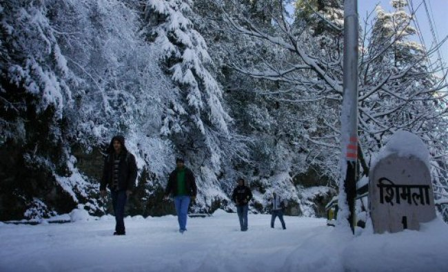 : People walk on a snow covered road after heavy snowfall in Shimla...