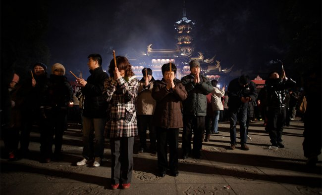 Worshippers burn joss sticks to pay their first visit of the \