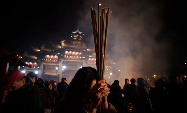 A worshipper burns joss sticks to pay her first visit of the \