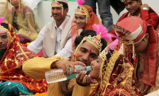A groom offers water to his bride during a mass marriage...