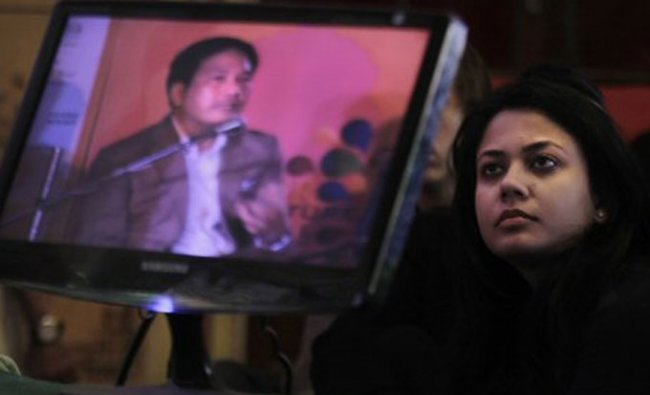 A reader listens to Burmese historian Thant Myint-U, seen on a television at the Literature festival