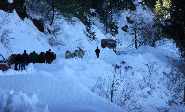 People walk on a snow covered road on the outskirts of Shimla