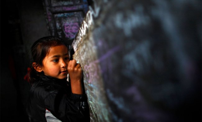 A Nepalese girl writes her name on the wall of the Saraswati Temple during Shri Panchami Festival