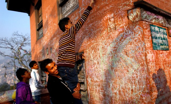 A Nepalese youth writes his name on the wall of the Saraswati Temple during Shri Panchami Festival