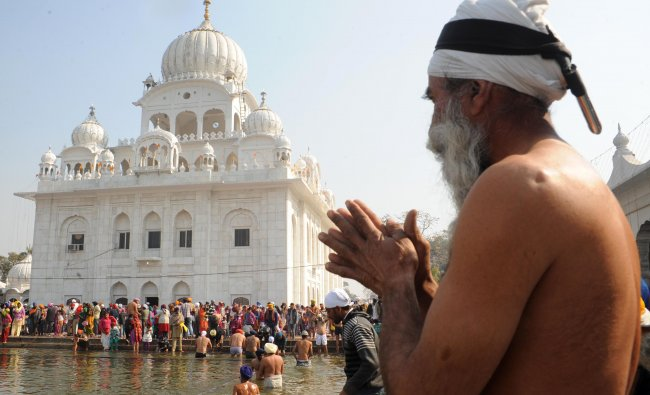 Indian Sikh devotees take a dip in the sarover