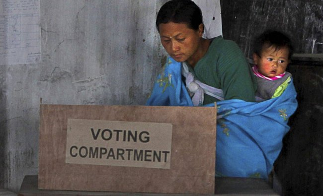 A woman with her child casts her vote