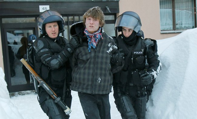Swiss riot police officers arrest a demonstrator during a demonstration against the WEF in Davos
