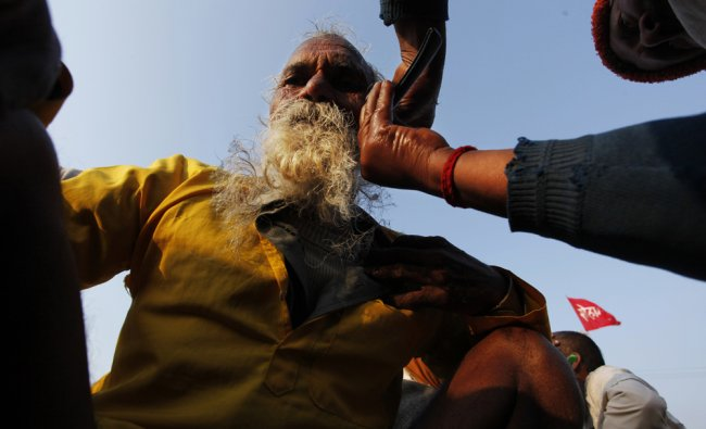 A Hindu devotee has his beard and hair cut at Sangam