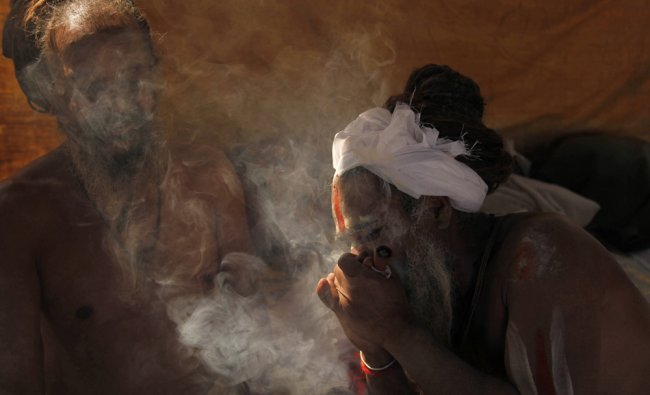 A Hindu holy man smokes marijuana at Sangam