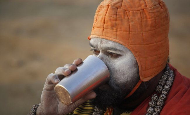 A Hindu holy man drinks tea at Sangam