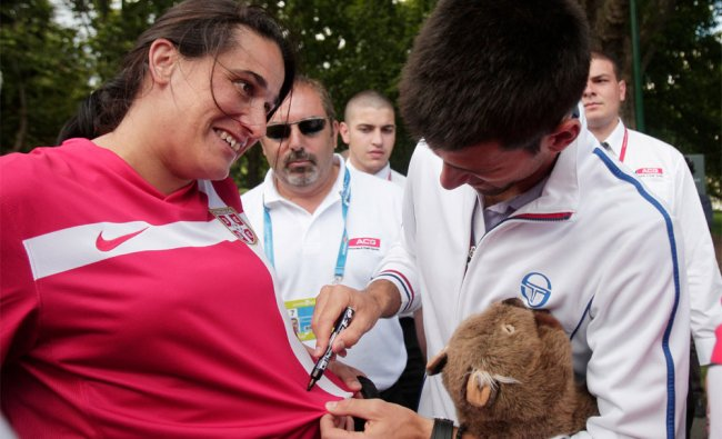Novak Djokovic signs his autograph onto the shirt of a fan