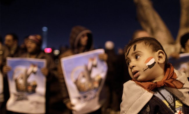 An Egyptian child is held by his father during a protest in Cairo