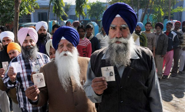 Voters show their identity cards as they wait to cast their votes at a polling station in Punjab
