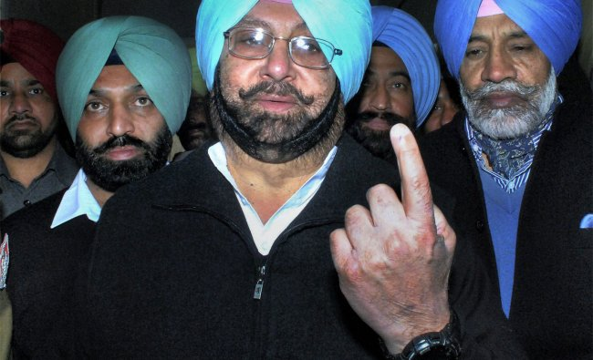 Captain Amarinder Singh shows his marked finger after casting his vote