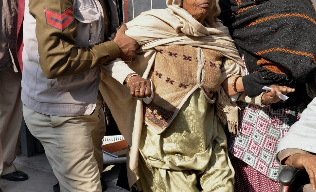 An elderly voter is assisted as she arrives to cast her vote