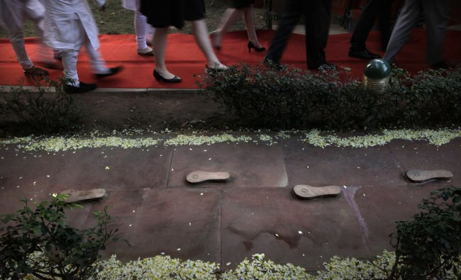 Visitors walk past the preserves of the footsteps which the late Mahatma Gandhi