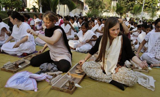 Students try their hand on the charkha at Satyagrah Ashram Samarak