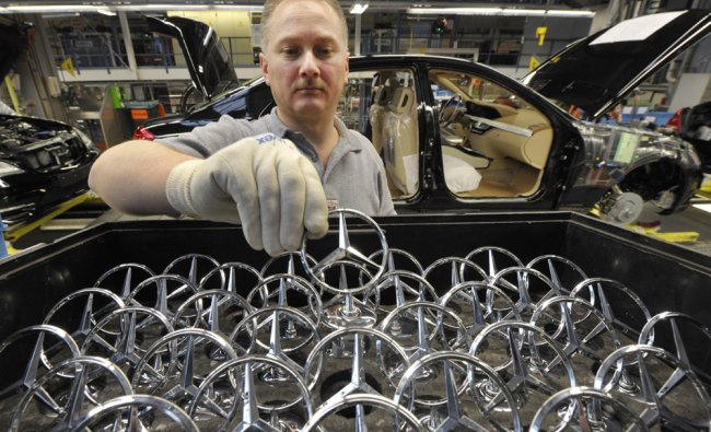 Employee of Mercedes-Benz takes a star to fix it on the hood of a S-class car