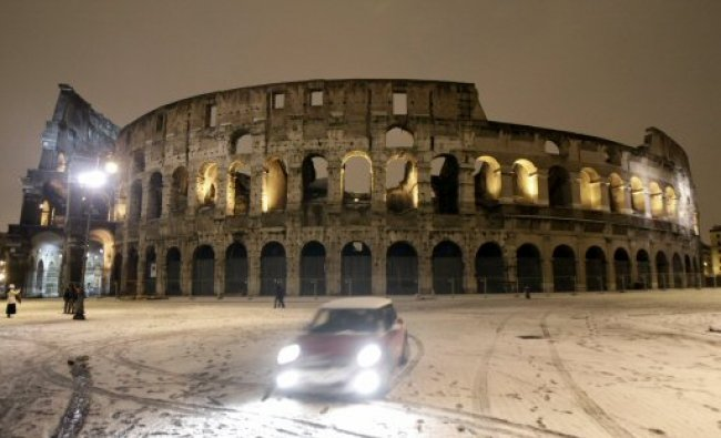 Ancient Colosseum after a snowfall blanketed the city of Rome