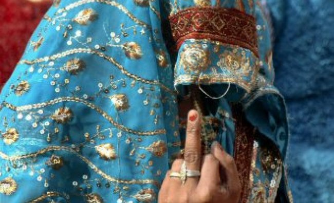 A woman voter shows her marked finger as she leaves after casting vote