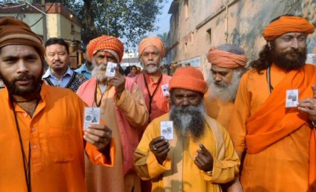 Sadhus show their identity cards after casting votes...